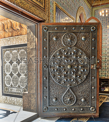 Opened wooden aged door with ornate bronzed floral patterns at the mosque of The Manial Palace of Prince Mohammed Ali Tewfik, Cairo, Egypt