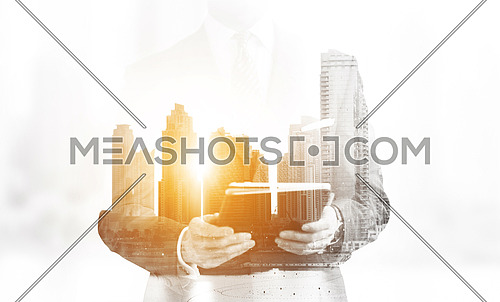 Double exposure of senior businessman with tablet and big city towers in the background