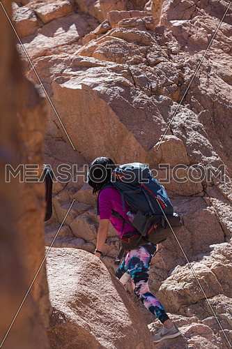 Long shot for group of tourists walking on big rocks explore Sinai Mountain for wadi Freij at day.
