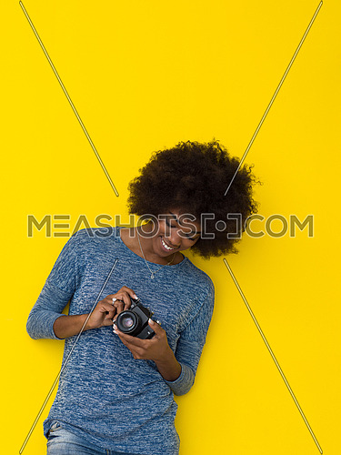 portrait of a smiling pretty african american girl taking photo on a retro camera isolated over yellow background