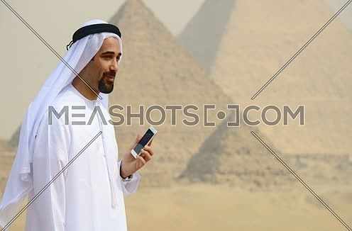 Emiratie man at the pyramids using mobile phone