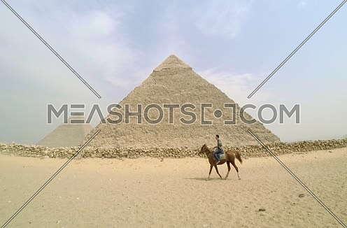 man riding horse by the pyramids of giza