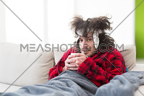 young Man in bathrobe with flu and fever wrapped holding cup of healing tea while sitting on sofa at home