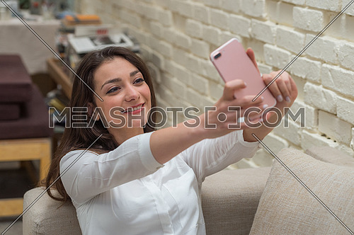 A young woman sits at home playing with mobile