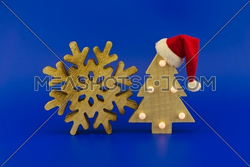 Snowflake decoration and Christmas tree with a Santa hat on top on a festive blue background. New Year and Christmas holiday season concept card decoration