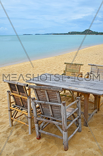 Wooden bamboo furniture, table and four chairs on sand beach with blue sea water and cloudy sky background