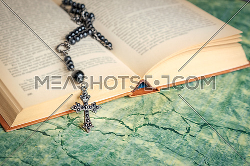 Black rosary and cross on the Bible on a green surface. Religion at school.