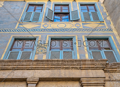 Facade of Beit (house) El Harrawi with glass windows, wooden grids and ornate wall painted in yellow and blue, an old Mamluk era eighteenths century historic house in Medieval Cairo, Egypt