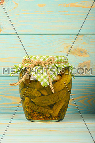 One glass jar of homemade pickled cucumbers with green checkered textile top decoration at blue painted vintage wooden surface