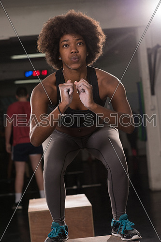 Fit young african american woman box jumping at a crossfit style gym. Female athlete is performing box jumps at gym.