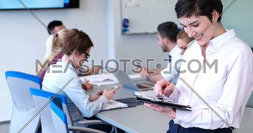 Businesswoman using tablet with coworkers in backgorund having meeting