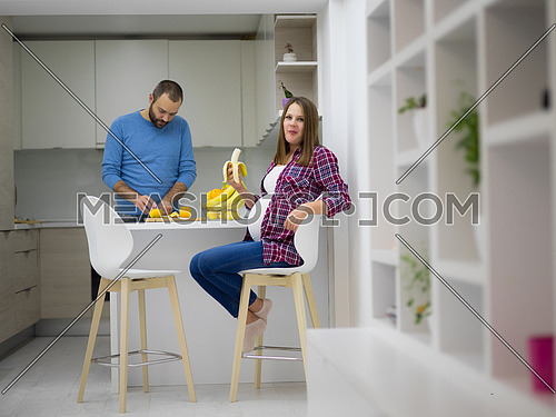 young pregnant couple cooking food fruit lemon juice at kitchen, lifestyle healthy pregnancy happy life concept