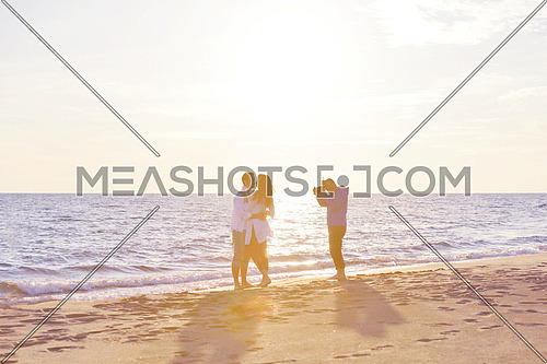 photographer taking photo of models couple on beautiful tropical beach at summer