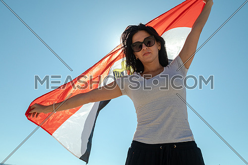 Low angel for Female tourists spreading Egyptian flag while exploring Sinai Trail from Ain Hodouda by day.