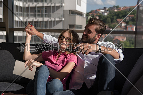 Young couple sitting on sofa near the window watching television together at luxury home