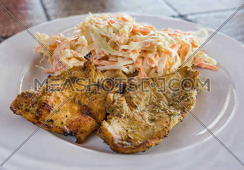 Pictured fillets grilled chicken with salad made from carrots, sauerkrauts and mayonnaise served on white plate.