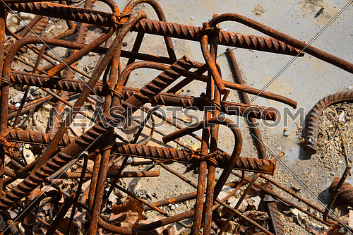 Rusty corroded stained metal pieces: wire, fitting, armature on a dirty concrete floor