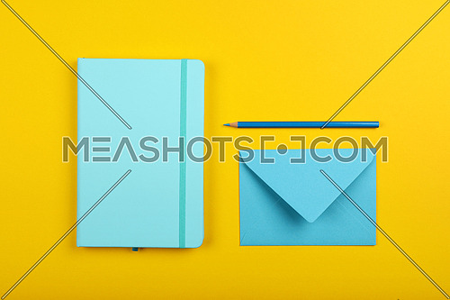 Neatly organized stationery flat lay of pastel blue notebook, envelope and pencil over yellow paper background, elevated top view, directly above