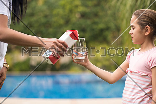Middle Eastern girl enjoying with a glass of milk in her hand outside on summer day