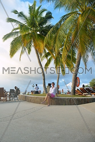 Beautiful young woman in bikini lying on a deckchair with a drink by the sea swimming pool and relax