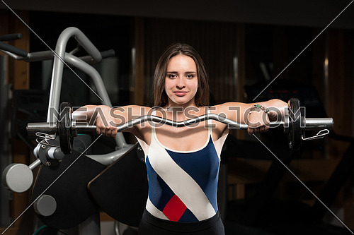 Young Woman Doing Heavy Weight Exercise For Trapezius