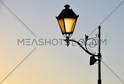Street antique style lamp post with effect of shine from low light of sunset