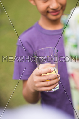 a  middle east boy with a glass hand cheerfully waiting healthy natural beverage outdoors