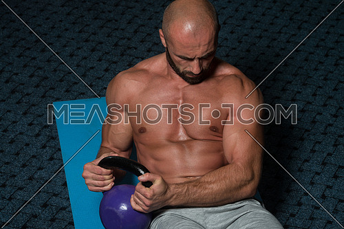 Muscular Man Exercising Abs Abdominals With Kettlebell On Floor
