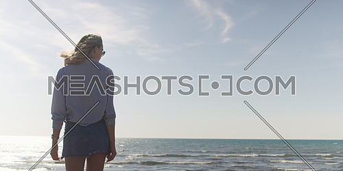 Young woman on the beach. The girl enjoying the warm autumn day. Portrait of beautiful girl near the water