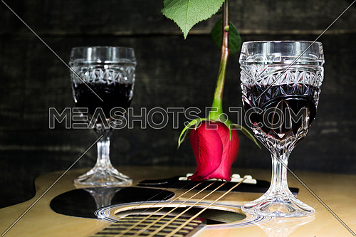 Glass Of Red Wine Resting on Acoustic Guitar With Red Rose and another Glass in The Background