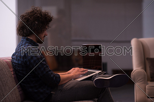 technology, home and lifestyle concept  of man working with laptop computer and sitting on sofaa
