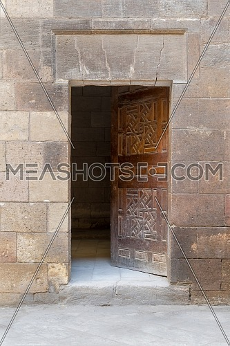 Wooden grunge old door and stone bricks wall, leading to Zeinab Khatoun old historic house, Old Cairo, Egypt