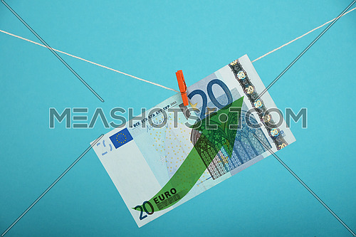 European economy growth, strengthening of Euro currency, twenty Euro banknote with green arrow up hanged ascending with pin at rope over blue
