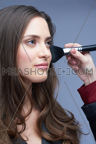 portrait of beautiful young woman portrait in studio during makeup apply
