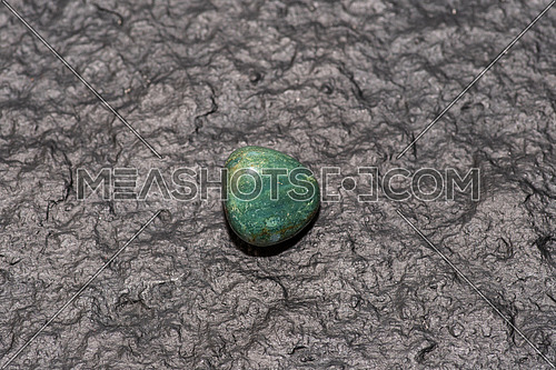 Prasiolite (green quartz) isolated on black stone background. Macro shot