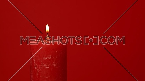 Close up one red candle trembling flame over vivid red background, off-center, fired up with lighter, burning and blown out, low angle side view