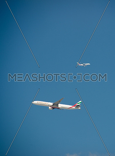 two emirates airlines aircrafts one landing one taking off in the same frame