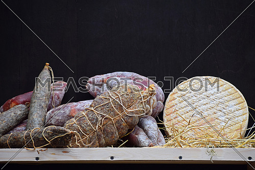Wooden shelf with gourmet artisan cheese and sausage selection, on straw over black board background, close up, low angle view