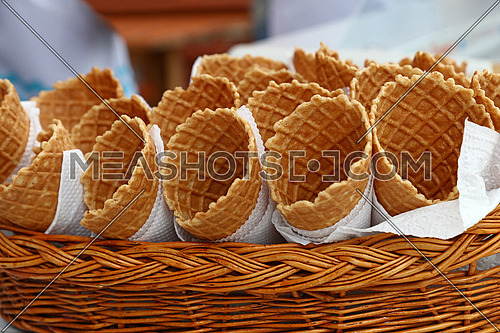 Several empty fresh wafer ice cream cone cornet cups with white paper napkins in wooden wicker basket display, close up, low angle side view
