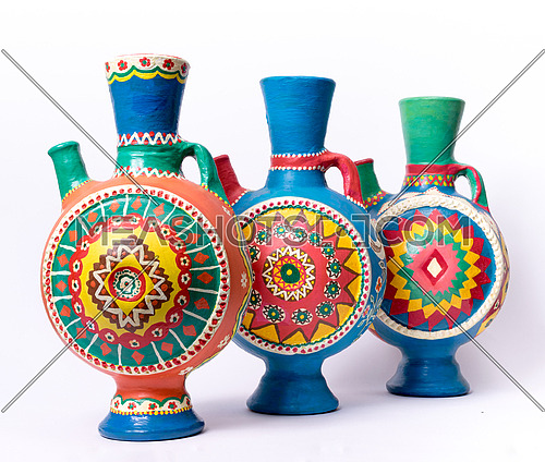 Still life of three decorated colorful handcrafted pottery jugs on white background