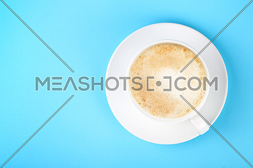 Close up one full white cup of frothy latte cappuccino coffee and saucer over pastel blue paper background, elevated top view, directly above