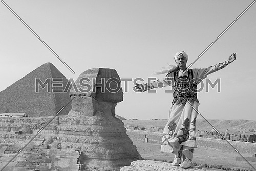 a black and white image of a traditional Egyptian sufi dancer performing at Giza pyramids