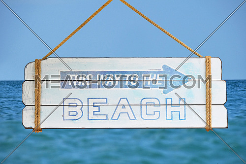 Close up old wooden directional arrow sign with this way to the beach text hanging over background of blue sky and sea