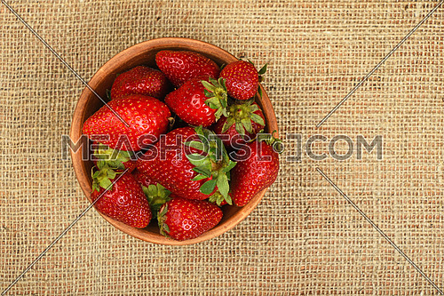 Mellow fresh red summer strawberries in rustic ceramic bowl on jute burlap canvas background, top view