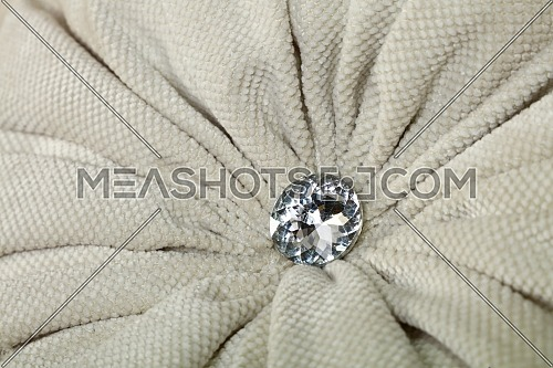 Close up diamond shaped crystal strass or rhinestone decoration on grey beige furniture textile upholstery
