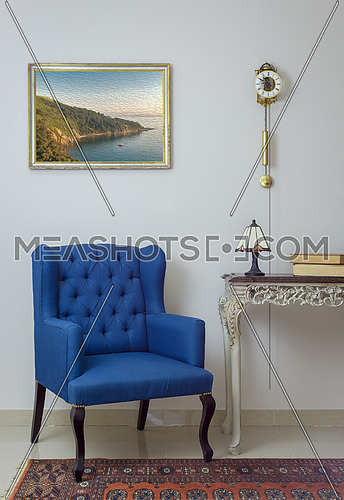 Vintage Furniture - Interior composition of retro blue armchair, vintage wooden beige table, table lamp, books, and pendulum clock over off white wall, tiled beige floor and orange ornate carpet