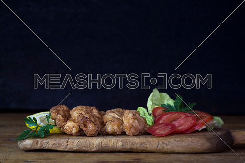 Breaded Chicken Meat With Salad And Lemon Resting On a Rustic Wooden Board