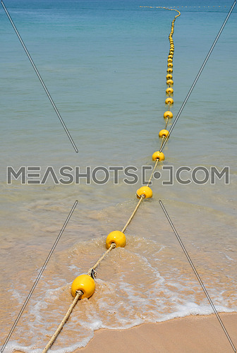 Chain of yellow polystyrene sea marker buoys with cable tow at sand beach and in blue sea water, perspective