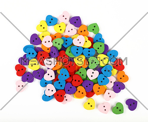 Mix of colorful multicolor heart shaped painted wooden handmade sewing buttons isolated on white, close up, elevated top view