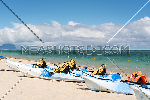 Blue and white kayaks with life jackets on sandy beach at Mauritius island,sunny day with clouds in the sky and mountain background.